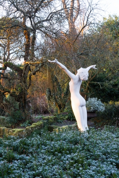 Winter in the formal Italianate garden at Borde Hill with a nude statue of a woman with outstretched arms in foreground