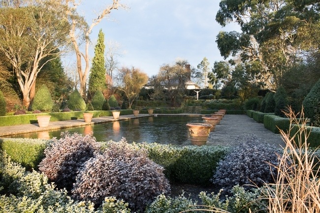 Winter in the formal Italianate garden at Borde Hill with a nude statue of a woman with outstretched arms in background