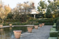 Terracotta containers around the edge of the frozen pool in the Italianate garden with rill in background