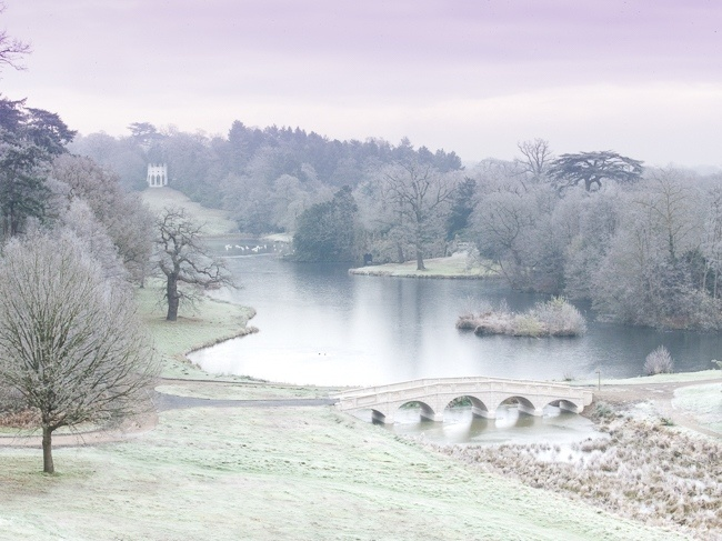 Painshill Park landscape garden overlooking the reinstated five arch bridge, frozen lake and grotto with the Gothic Temple in the background
