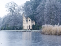 Painshill Park landscape garden overlooking the frozen lake with the Ruined Abbey in the background